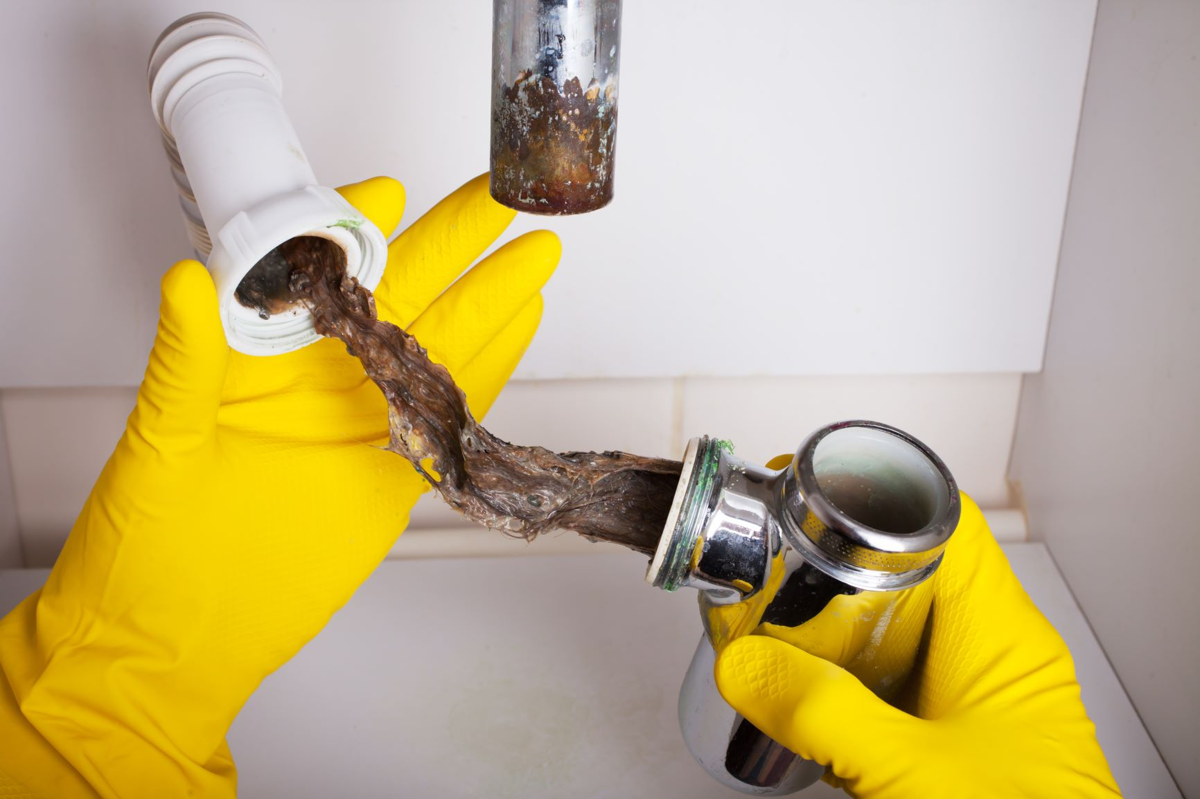 Man With Yellow Gloves Fixing a Clogged Pipe With Hydro Jetting