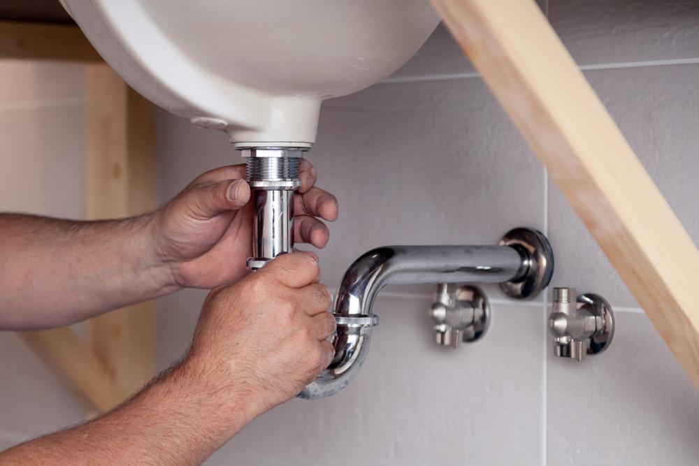 Man Repairing The Drain Pipe Under The Sink